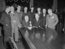 Titre original :  Newfoundland and Canadian Government delegation signing the agreement admitting Newfoundland to Confederation. Prime Minister Louis S. St. Laurent and Hon. A.J. Walsh shake hands following signing of agreement.