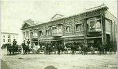Titre original :  Courtesy Saskatoon Public Library. Street view of J.F. Cairns Store, 204-222 2nd Avenue South (near corner of 21st Street), next to corner he sold to Bank of Commerce. Lined up in street are nattily dressed men with horses and buggies. [before July 1912] Creator/Photographer:	McKenzie, Peter.