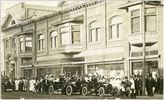 Titre original :  Courtesy Saskatoon Public Library. Crowd in front of J. F. Cairns store on 2nd Avenue South admire passing automobiles. between 1906 and 1912