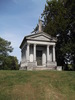Original title:  Sanford Mausoleum. After Jackson Sanford's death from tuberculosis in 1897, Senator Sanford engaged the New York City firm of C.E. Tayntor & Co. to design a mausoleum for his son, and for future use by the family. Built of Vermont granite, it was rumoured to cost $100,000. The Senator's remains were the first to be placed here, in 1899, to be followed by Jackson Sanford, and his infant son Harry Vaux Sanford, who had died in 1872. This mausoleum is located in the Hamilton Cemetery. Photo by Paul Grimwood, used with permission.
