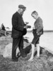 Original title:  John Macoun and young friend examining bird's nest and egg.