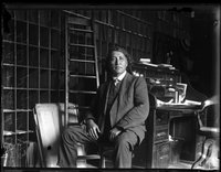 Original title:  Glass negative (black and white); portrait of John Ojijatekha Brant-Sero, a Mohawk loyalist, seated inside a study, wearing a three piece suit; bookcases, a desk, a ladder and a chair are behind him; Canada.  Photographic process