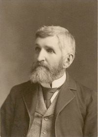Titre original :  Black and white photograph of man in a suit with full beard