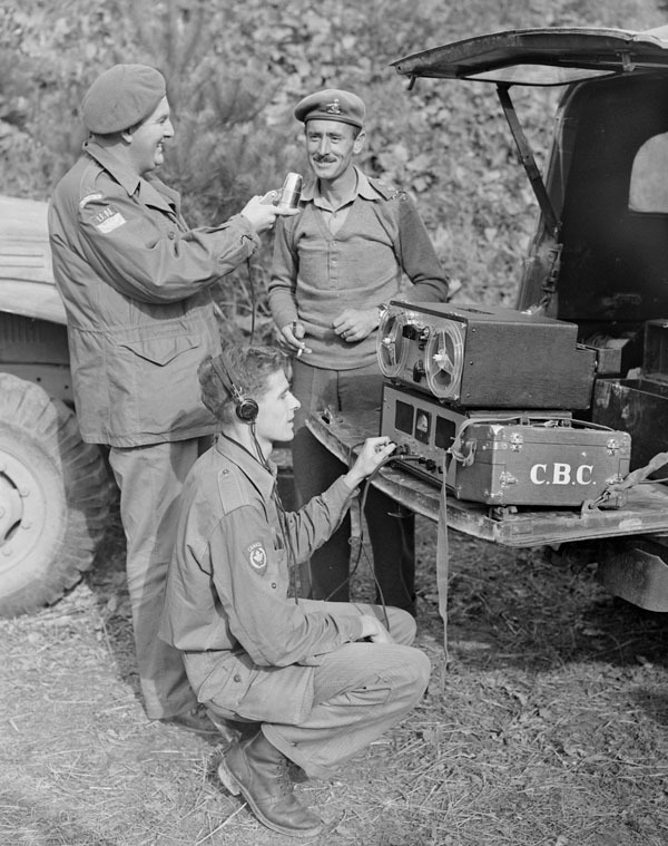 Titre original :  Normand Eaves, at the mike, and Norman McBain, at the controls, interviewing Lt. Col. James Dextraze, commanding officer of the Royal 22nd Regiment.